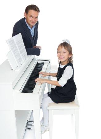 Photo pour La jeune fille à l'école de musique apprendre avec diligence à jouer de la musique de piano, que son professeur de musique - Isolé sur fond blanc - image libre de droit