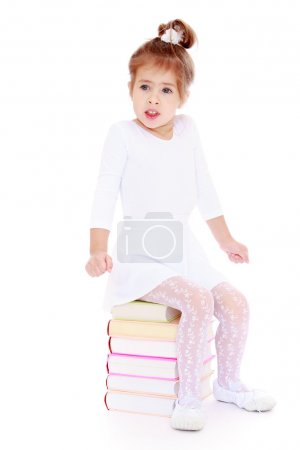 Photo pour Little girl froze while sitting on a stack of books.Isolated on white background, Lotus Childrens Center - image libre de droit