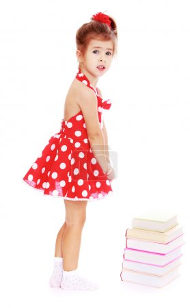 Photo pour Adorable little girl in a short red dress standing next to a book lying on the floor.Isolated on white background, Lotus Childrens Center - image libre de droit