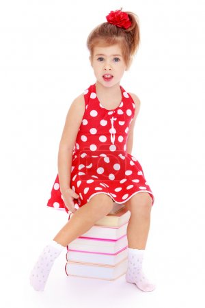 Charming little girl in a red dress sitting on the...