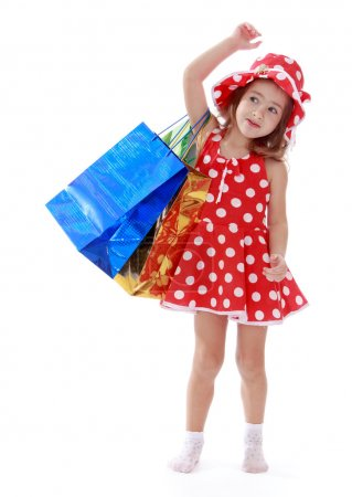 Foto de Little girl in a summer dress with polka dots is on the shoulder of shopping bags.Isolated on white background, Lotus Childrens Center - Imagen libre de derechos