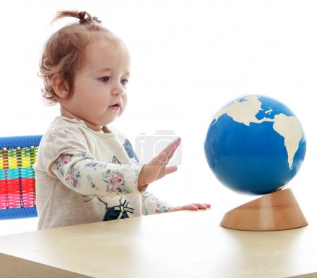 Foto de Very small but serious little girl spinning globe hand.Isolated on white background, Lotus Childrens Center - Imagen libre de derechos