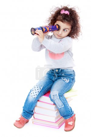 romantic little girl with curly hair sitting on a pile of books