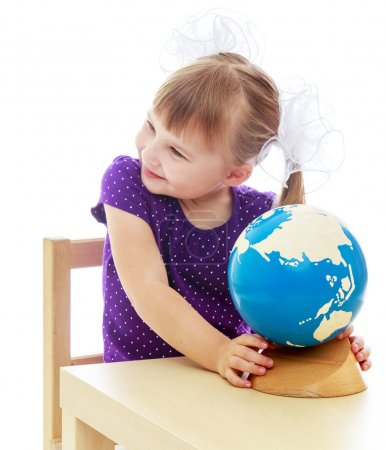 Adorable little girl looking at a globe and dreams of where she
