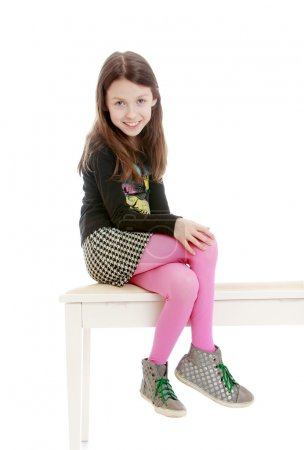 Stylish long-haired girl in a short skirt and pink tights sits o