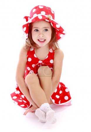 Adorable little girl in a red dress and hat with polka dots sitt