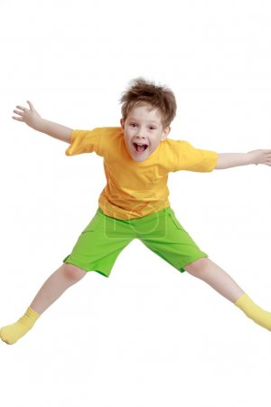 Little boy in yellow t-shirt and shorts jumping