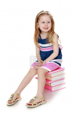 The child sits on the books