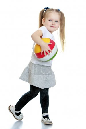 Photo for Cute little blonde girl with her hair plaited in long tails in a white t-shirt with short sleeves and a grey short skirt keeps hand striped rubber ball, pictures in motion- isolated on white - Royalty Free Image