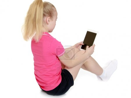 The girl looks at the screen of a smartphone