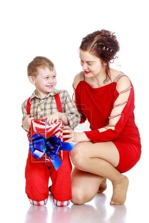 Photo pour Petit garçon joyeux et joyeux dans une chemise à carreaux et de longs shorts rouges tenant une boîte magnifiquement enveloppée décorée d'un arc. Dans la boîte est un cadeau qu'il a donné à sa mère bien-aimée. Avec ma mère - image libre de droit
