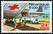NICARAGUA - CIRCA 1984: A stamp printed in Nicaragua from the  50th anniversary of Nicaraguan Red Cross  issue shows Red Cross airplane and ambulance, circa 1984.
