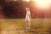 Dívka v parku v bílých šatech za slunečného dne