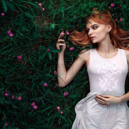 fabulous portrait woman lying down in field with flowers