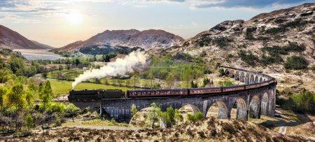 Photo pour Glenfinnan Railway Viaduc en Écosse avec le train à vapeur jacobite contre le coucher du soleil sur le lac - image libre de droit