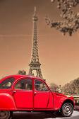 Eiffelova věž s staré červené auto v Paříži