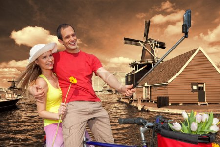 Couple Taking Selfie against  windmills in Zaanse Schans, Amsterdam