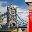 Tower Bridge with red phone booths in London, Engl...
