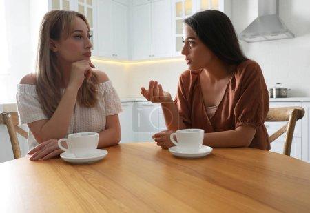 Les jeunes femmes parlent tout en buvant du thé à table dans la cuisine