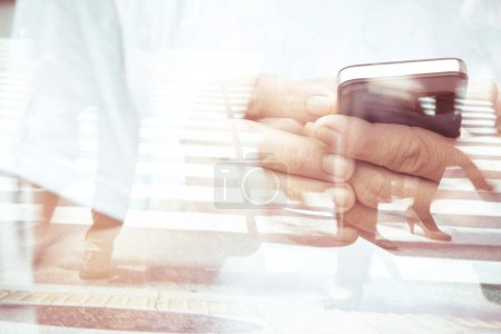 Double exposure of man using smart phone