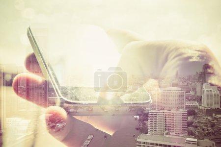 Foto de Doble imagen de exposición de las personas con smart teléfono y paisaje urbano, concepto de negocio tecnología. - Imagen libre de derechos