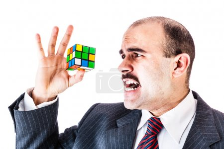 businessman trying to solve a cube puzzle