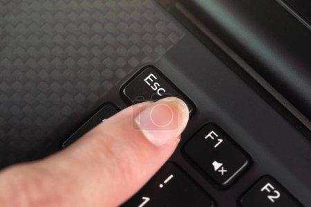 Detalle en el dedo de la mujer presionando la tecla esc en el teclado portátil