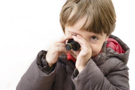 Cute boy playing with miniature camera