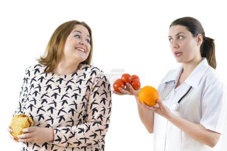 Photo pour Médecin conseillant à une grosse femme de manger sainement. Grosse femme mangeant furtivement des aliments riches en calories . - image libre de droit