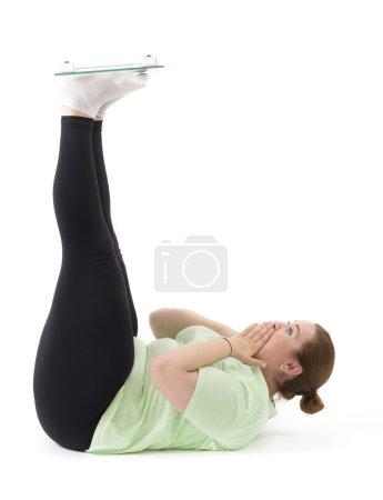 Photo pour Drôle de grosse femme tenant la machine de pondération à l'envers - image libre de droit