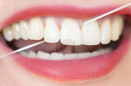 Photo pour Femme utilisant de la soie dentaire - image libre de droit