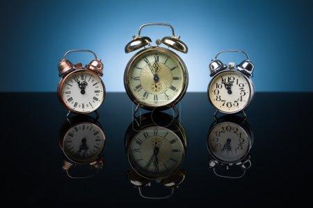 Photo for Vintage alarm clocks showing five minutes to twelve, blue background - Royalty Free Image