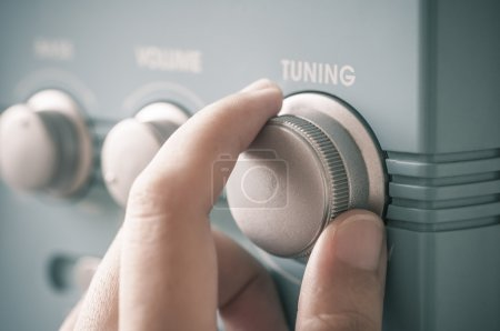 Hand tuning fm radio button. Retro image processed...