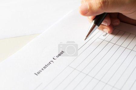 Photo pour Femmes mains avec un stylo sur papier en compte l'inventaire avec la liste des tables d'écriture. - image libre de droit