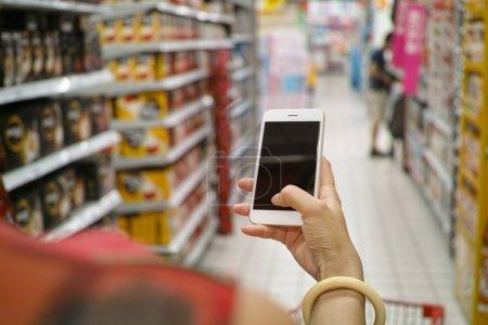 Photo pour Un acheteur utilisant un téléphone portable dans un supermarché - image libre de droit
