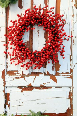 Photo for Christmas wreath of red holly berries against a vintage wooden door - Royalty Free Image