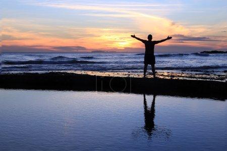 Photo pour Homme aux bras tendus au coucher du soleil sur une plage . - image libre de droit