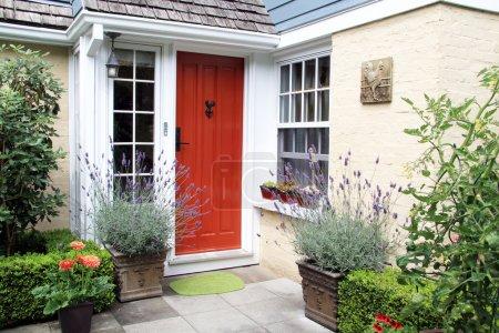 Photo pour Porte d'entrée rouge charmante avec la lavande fleurante dans des récipients. - image libre de droit