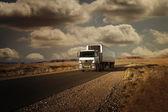 Auto na silnici v poušti na cestách při západu slunce