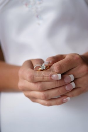 Bride holding her engagement ring.
