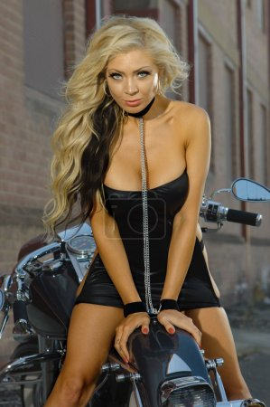 Sexy motorcycle biker girl wearing leather outfit