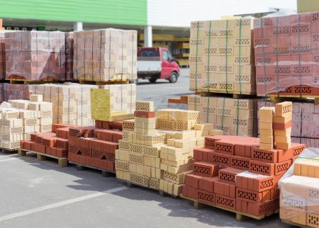 Pallets of perforated red and yellow bricks on warehouse