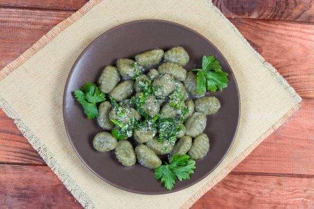 Photo pour Gnocchis de pommes de terre cuits avec sauce blanche assaisonnée aux épinards et légumes verts hachés sur un plat brun sur la table rustique, vue sur le dessus - image libre de droit