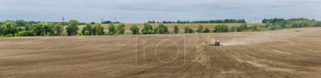 Plowed field with tractors