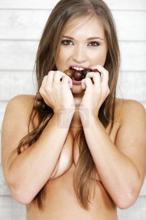 Topless woman biting beads