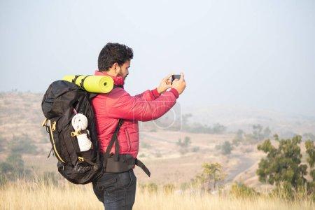 Photo pour Jeune voyageur avec sac à dos photographiant le paysage à l'aide d'un appareil photo mobile au-dessus de Mountian - concept de photographie de voyage et d'aventure pendant le trekking - image libre de droit