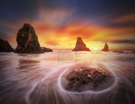 Photo pour C'est une photo de paysage marin avec des piles, flux océanique, soleil couchant et nuages colorés . - image libre de droit
