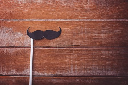 Black mustache paper on wooden background, Prostate cancer awareness month, Fathers day, minimal November moustache concept