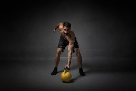 man with kettleball on hand