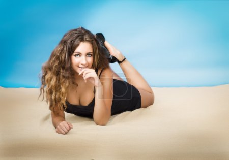 Model with curly hair in fashion pose lyind down
